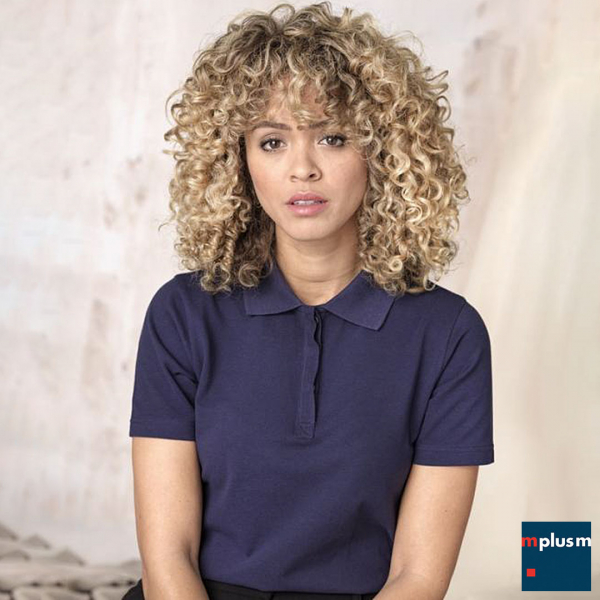 Model trägt nachhaltiges Poloshirt in navy. Mit Logo bedrucken